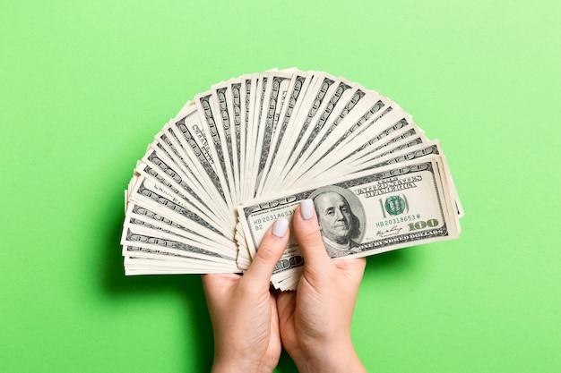 Un fan di cento banconote in dollari in mano femminile su variopinto. concetto di investimento
