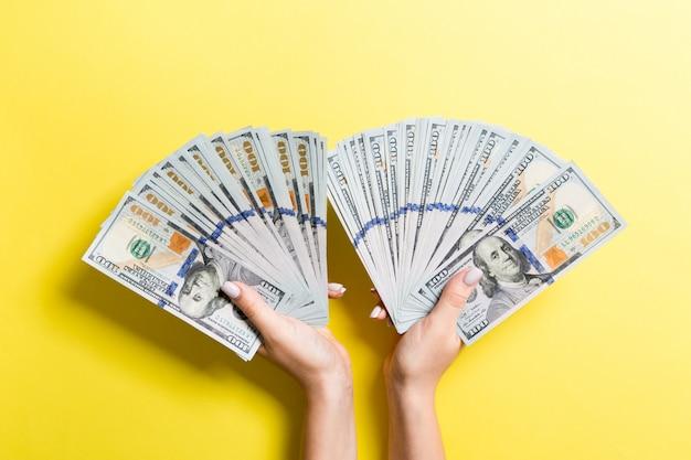 Un fan di cento banconote in dollari in mano
