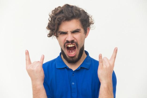 Un fan pazzo del rock e del metallo che fa le corna da diavolo