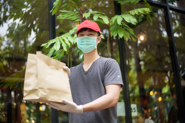 Un fattorino asiatico indossa la maschera, tiene la borsa della spesa, concetto di consegna a domicilio di sicurezza