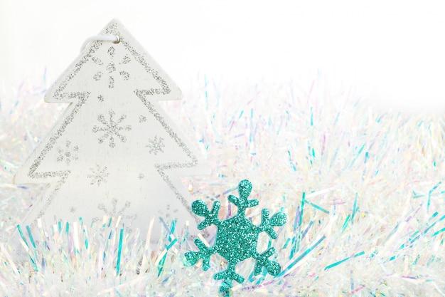 Un fiocco di neve blu lucido e una figurina di albero di natale bianca e argentata su tinsel blu e bianco. sfondo bianco. spazio per copia.