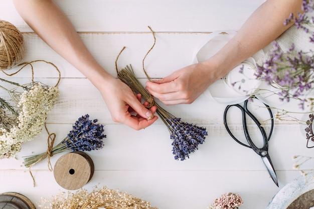 Un fioraio che lavora con fiori secchi