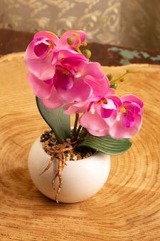 Un fiore rosa di vista frontale dentro piccolo vasino bianco sulla natura marrone dei fiori della scrivania