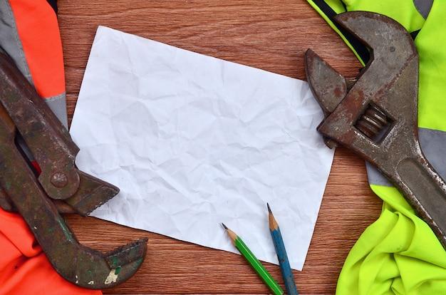 Un foglio di carta accartocciato con due matite circondate da divise da lavoro verdi e arancioni e chiavi inglesi regolabili