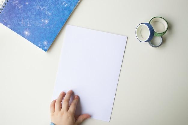 Un foglio di carta bianco, una nota blu con fiocchi di neve, nastro adesivo decorativo colorato e mano del bambino. il concetto di concentrazione, inverno e piani per il prossimo anno.