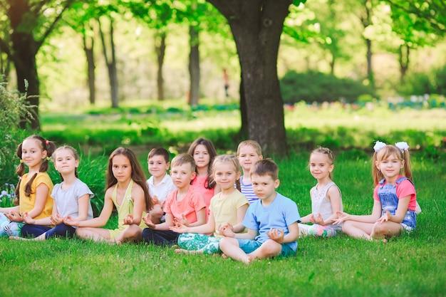 Un folto gruppo di bambini impegnati nello yoga nel parco seduto sull'erba.