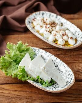 Un formaggio bianco di vista superiore con insalata verde sul formaggio da colazione del pasto dell'alimento dello scrittorio di legno marrone