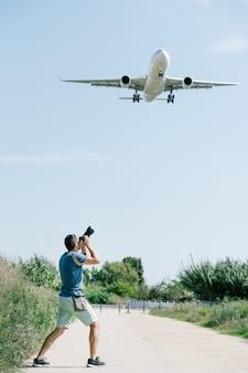 Un fotografo che scatta una foto di un aereo in decollo