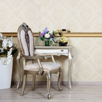 Un frammento di un interno retrò con una sedia e una scrivania su cui si trova un telefono e un vaso di fiori