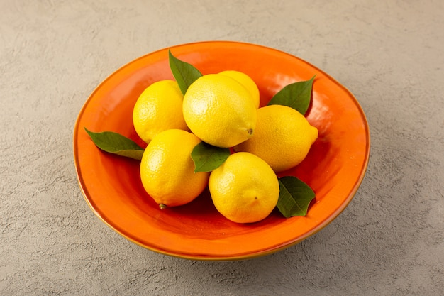 Un fronte chiuso chiuso giallo limoni freschi maturi succosi all'interno piatto arancione sul grigio