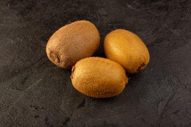 Un fronte chiuso chiuso kiwi marrone freschi maturi isolati succosi frutti morbidi e interi frutti sullo sfondo scuro frutta esotica fresca
