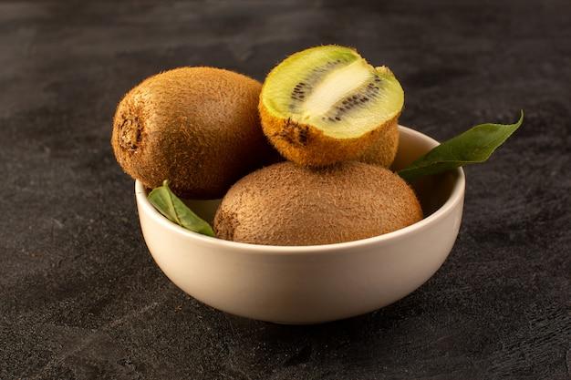 Un fronte chiuso chiuso kiwi marroni freschi maturi isolati succosi frutti morbidi e interi insieme con foglie verdi all'interno del piatto bianco