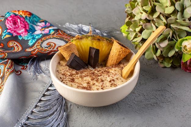Un fronte chiuso vista choco dessert marrone con fetta di ananas choco bar gelato all'interno del piatto bianco insieme a tessuto e fiori sul grigio