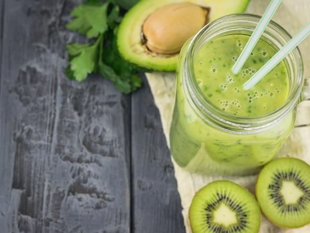 Un frullato appena preparato di avocado, banana, arancia, limone e kiwi su un tavolo di legno. dieta cibo vegetariano. cibi crudi.
