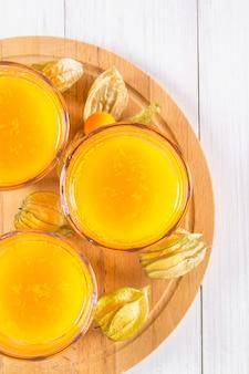 Un frullato di arancia fatta di physalis su un tavolo di legno bianco.