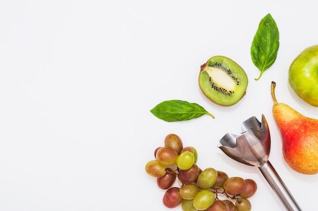 Un frullatore elettrico a mano con kiwi; mela; pera; uva e foglie di basilico su sfondo bianco