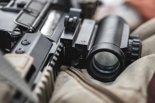 Un fucile d'assalto giace con un occhio su una valigetta militare.