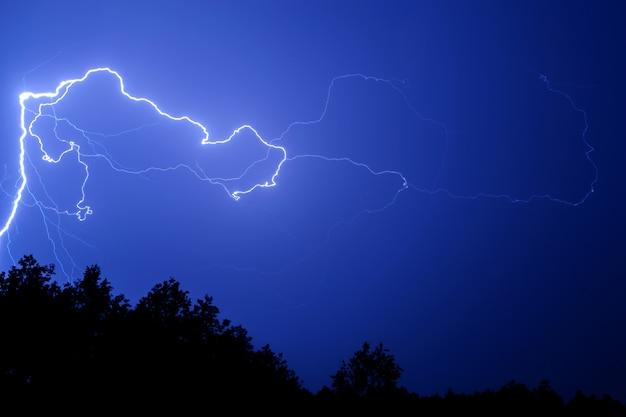 Un fulmine contro un cielo notturno blu sopra gli alberi.