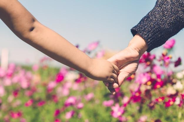 Un genitore tiene la mano di un bambino piccolo