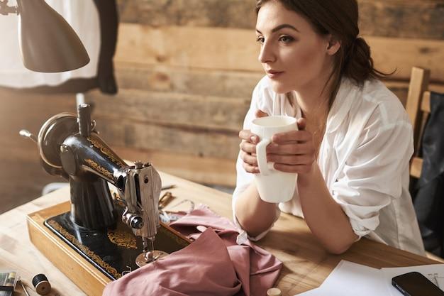 Un giorno la mia linea di moda diventerà famosa. sarto femminile sognante che pensa e beve il caffè, seduto vicino alla macchina per cucire e al tessuto, avendo pausa durante la creazione di un nuovo capo. la creatività preferisce non correre