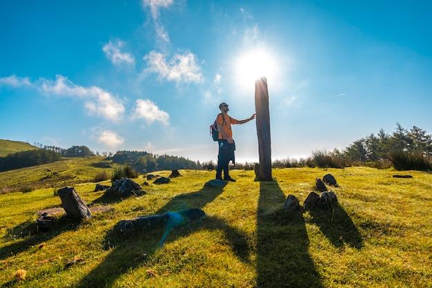 Un giovane accarezza un dolmen dalla cima del monte adarra a urnieta, vicino a san sebastian. gipuzkoa, paesi baschi