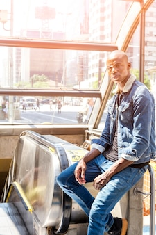 Un giovane africano seduto sulla scala mobile all'ingresso del sottopassaggio della città