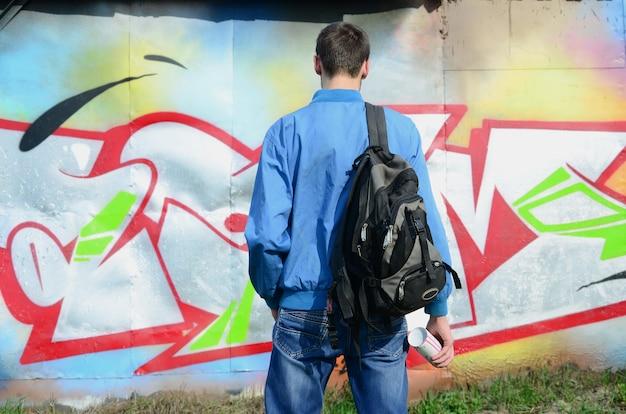 Un giovane artista di graffiti con una borsa nera guarda al muro