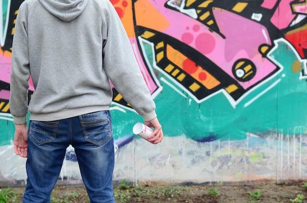 Un giovane artista di graffiti in una felpa con cappuccio guarda al muro