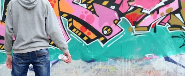 Un giovane artista di graffiti in una felpa grigia guarda al muro