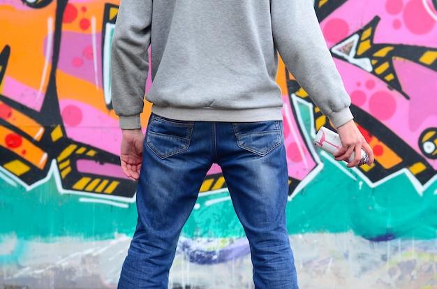 Un giovane artista di graffiti in una felpa grigia guarda il muro con