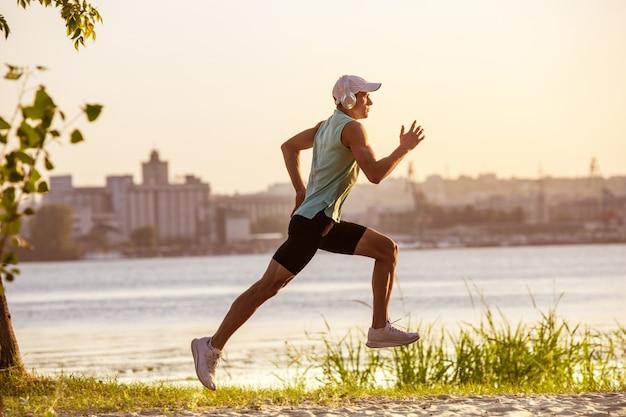 Un giovane atletico che risolve ascoltando la musica all'aperto sulla riva del fiume