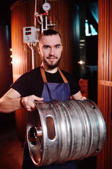 Un giovane bel birraio maschio detiene una botte di ferro con birra sullo sfondo del birrificio e serbatoi di birra
