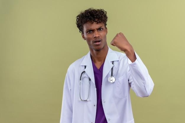 Un giovane bel dottore di carnagione scura con capelli ricci che indossa camice bianco con uno stetoscopio con espressione aggressiva che mostra il pugno chiuso su uno spazio verde