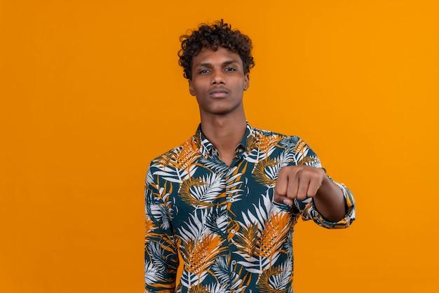 Un giovane bell'uomo dalla carnagione scura con i capelli ricci in foglie ha stampato la camicia che punta alla telecamera con il pugno chiuso
