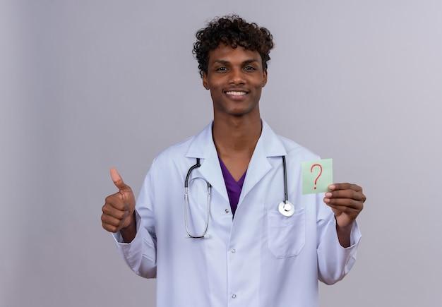 Un giovane bello di carnagione scura medico maschio con i capelli ricci che indossa mantello bianco con uno stetoscopio che mostra una carta di carta con il punto interrogativo