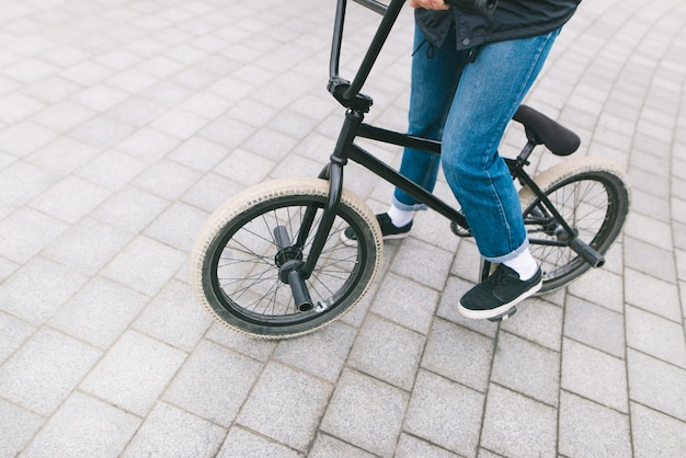 Un giovane chelovek siede su una bici bmx. bmx con gambe ravvicinate. concetto bmx. cultura di strada