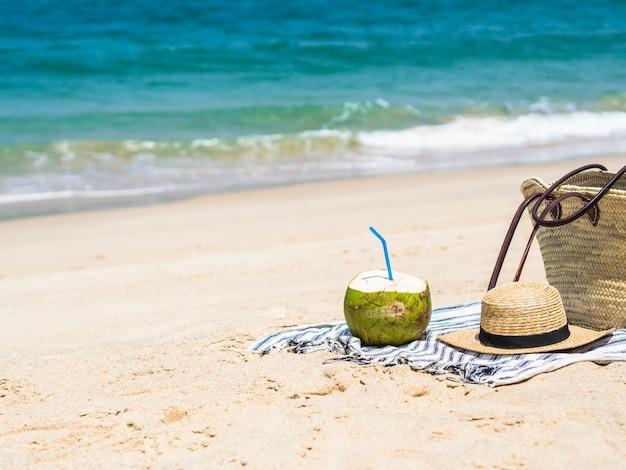 Un giovane cocco fresco è pronto da mangiare e una borsa di paglia e un cappello di paglia da donna su un asciugamano su una spiaggia sabbiosa contro un mare blu. concetto di viaggio vacanza tropicale. copia spazio