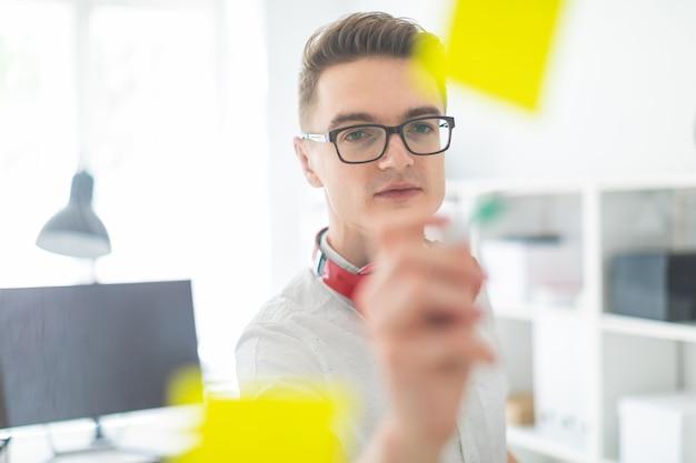 Un giovane con gli occhiali scrive adesivi incollati al vetro. al collo di un giovane che appende le cuffie.