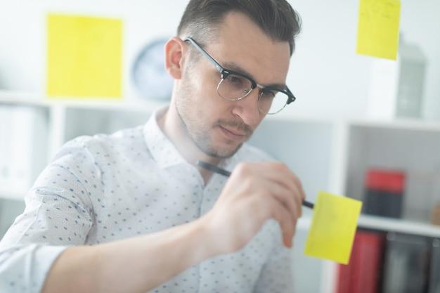 Un giovane con gli occhiali sta vicino a una tavola con adesivi e li scrive con una matita.
