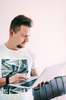 Un giovane con la barba e una maglietta bianca lavora a casa su un laptop in quarantena. ritratto del primo piano espressione facciale seria. resta a casa concetto. sfondo luminoso. copyspace