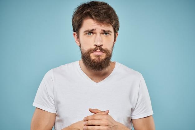 Un giovane con la barba in maglietta mostra emozioni diverse, divertimento, tristezza, rabbia nello spazio