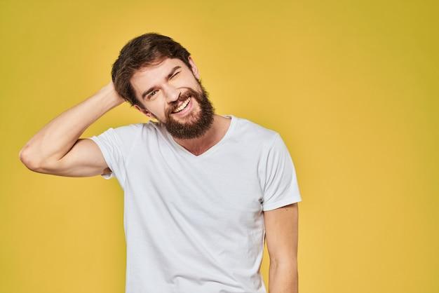 Un giovane con la barba in maglietta mostra emozioni diverse