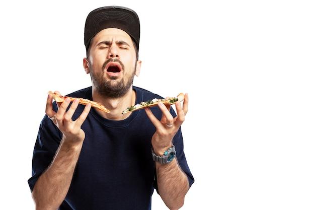 Un giovane con un berretto mangia la pizza con piacere. isolato su sfondo bianco. spazio per il testo.