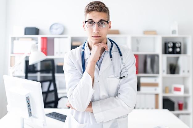 Un giovane con una tunica bianca è in piedi in ufficio e si è appoggiato il mento con la mano.