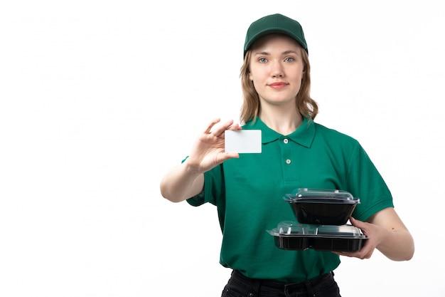 Un giovane corriere femminile di vista frontale in ciotole verdi della tenuta dell'uniforme con la carta bianca dell'alimento e sorridere sul bianco