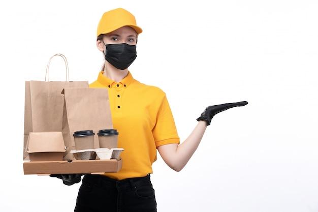 Un giovane corriere femminile di vista frontale in guanti neri uniformi gialli e maschera nera che tiene tazze e pacchetti di caffè