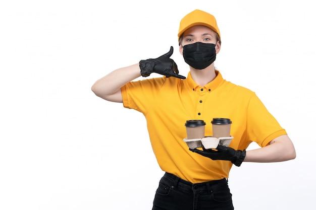 Un giovane corriere femminile di vista frontale in guanti neri uniformi gialli e mascherina nera che tiene le tazze di caffè che trasportano l'ordine che chiede di chiamare