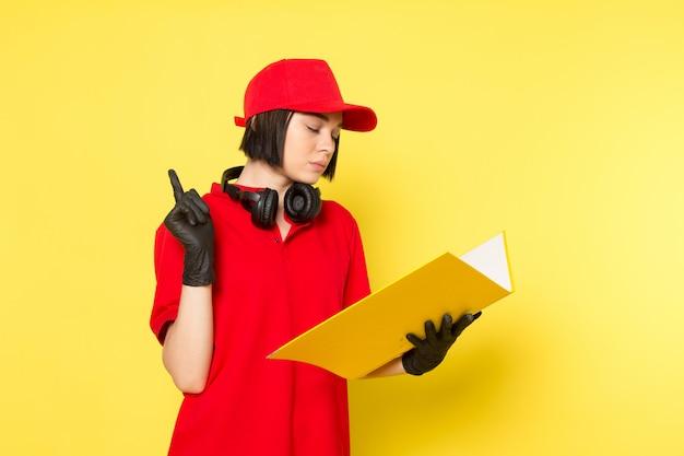 Un giovane corriere femminile di vista frontale in guanti neri uniformi rossi e spiritello malevolo che tengono archivio giallo