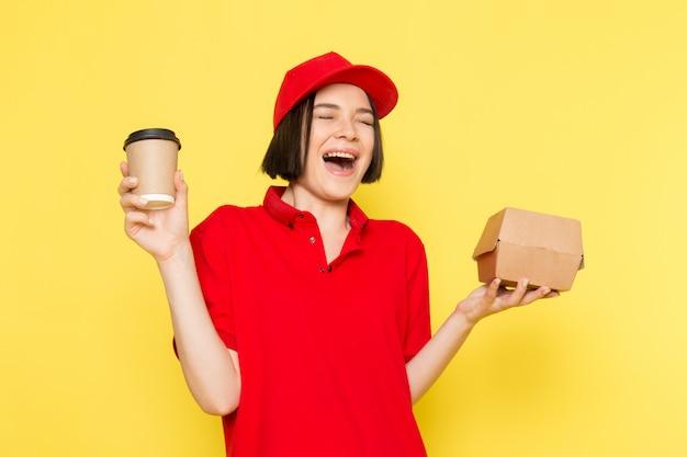 Un giovane corriere femminile di vista frontale in guanti neri uniformi rossi e spiritello malevolo che tengono scatola e tazza di caffè di alimento