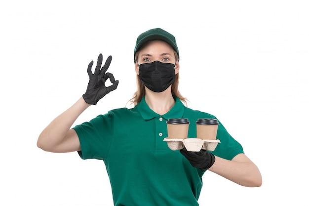 Un giovane corriere femminile di vista frontale in guanti neri uniformi verdi e mascherina nera che tengono le tazze di caffè